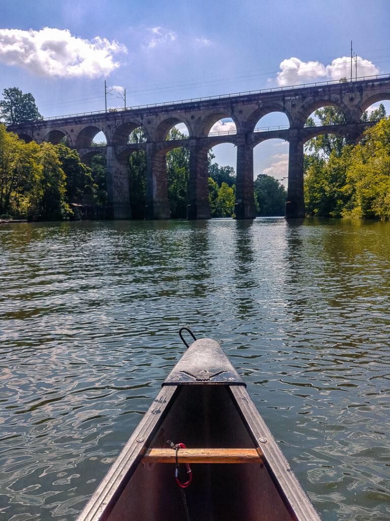 Mit dem Kanu geht es unter dem Viadukt hindurch